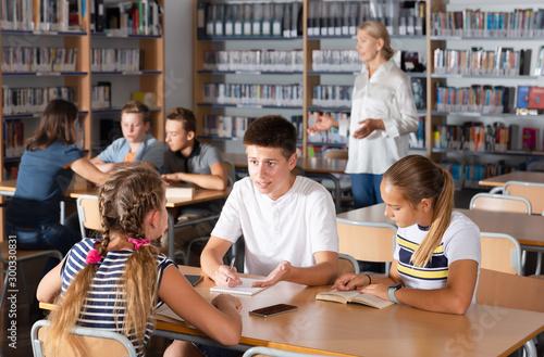Obraz Attentive boys and girls brainstorming in teams - fototapety do salonu