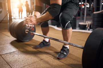 Close up of young active powerlifter dressed in black sporty shorts and t shirt, bending in front of heavy barbell, clapping hands using powder, preparing for deadlift, workout concept, side shot