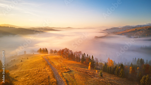 Sea of fog in mountain valley. Awesome alpine highlands. Wallpaper Mural