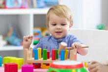 Kid Boy Plays With Educational Toy At Home Or Creche