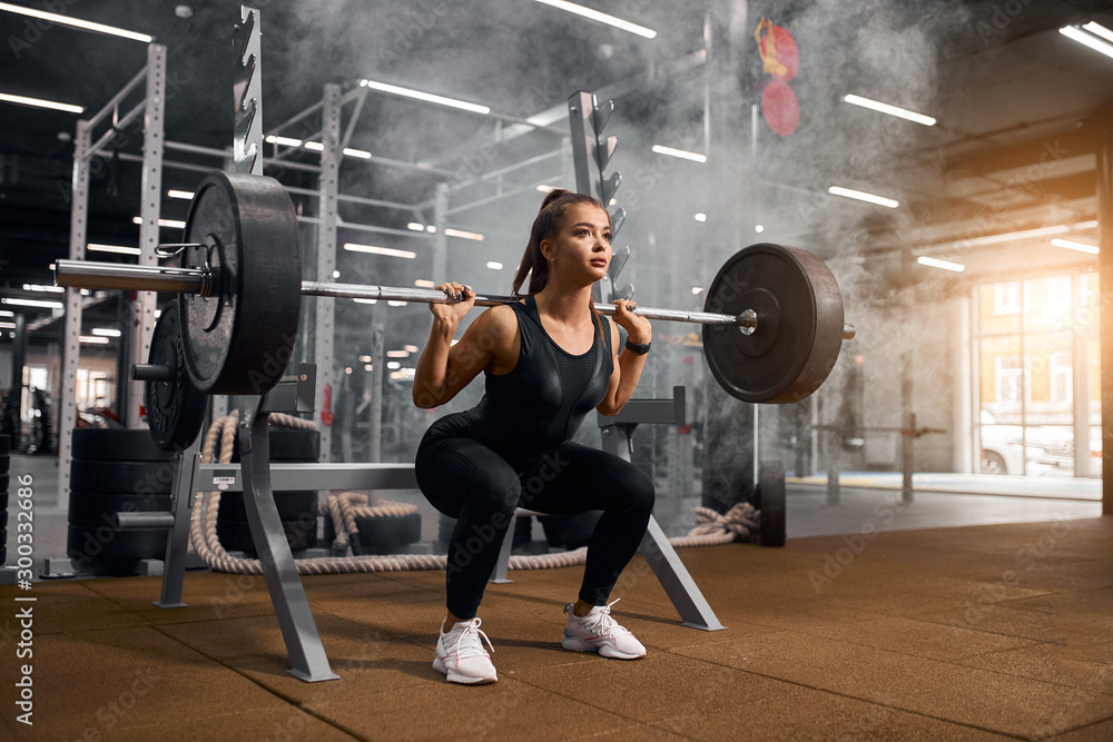 Fototapety, obrazy: Beautiful young powerlifter squatting in modern fitness studio using heavy barbell, looking aside expressing self assurance, professional sport concept, white smoke in the air