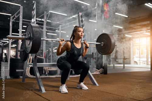 Obraz na plátně  Beautiful young powerlifter squatting in modern fitness studio using heavy barbe