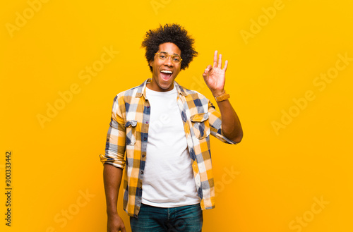 Valokuva  young black man feeling successful and satisfied, smiling with mouth wide open,
