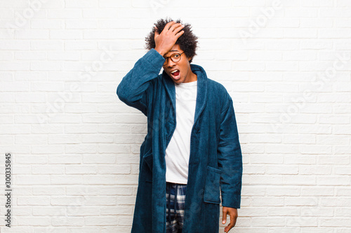 young black man wearing pajamas with gown raising palm to forehead thinking oops Tablou Canvas