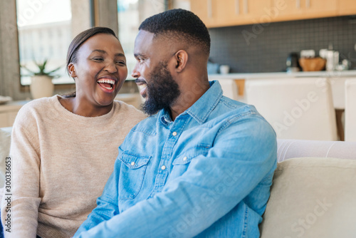 Obraz Young African American couple sitting on their sofa and laughing - fototapety do salonu