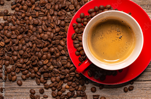 Wall Murals Cafe Red cup of aromatic black coffee on a wooden table.