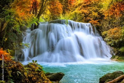Colorful majestic waterfall in national park forest during autumn - Image