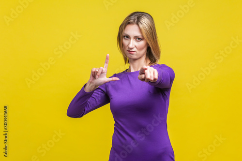 You are loser! Portrait of bossy serious businesswoman in elegant purple dress showing loser gesture and pointing at camera, accusing for failure Canvas-taulu