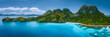 Leinwanddruck Bild - Aerial drone panoramic view of uninhabited tropical island with rugged mountains, rainforest jungle, sandy beaches surrounded by blue ocean