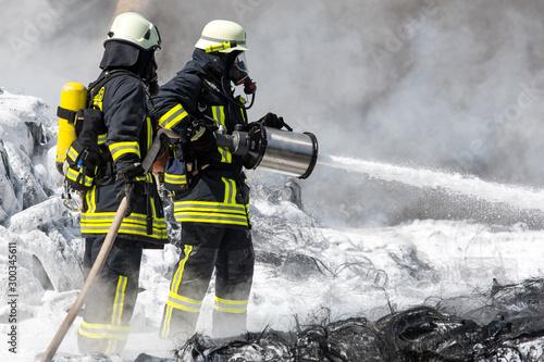 Valokuva  Feuerwehr löscht mit Wasser und Schaum brennende Reifen