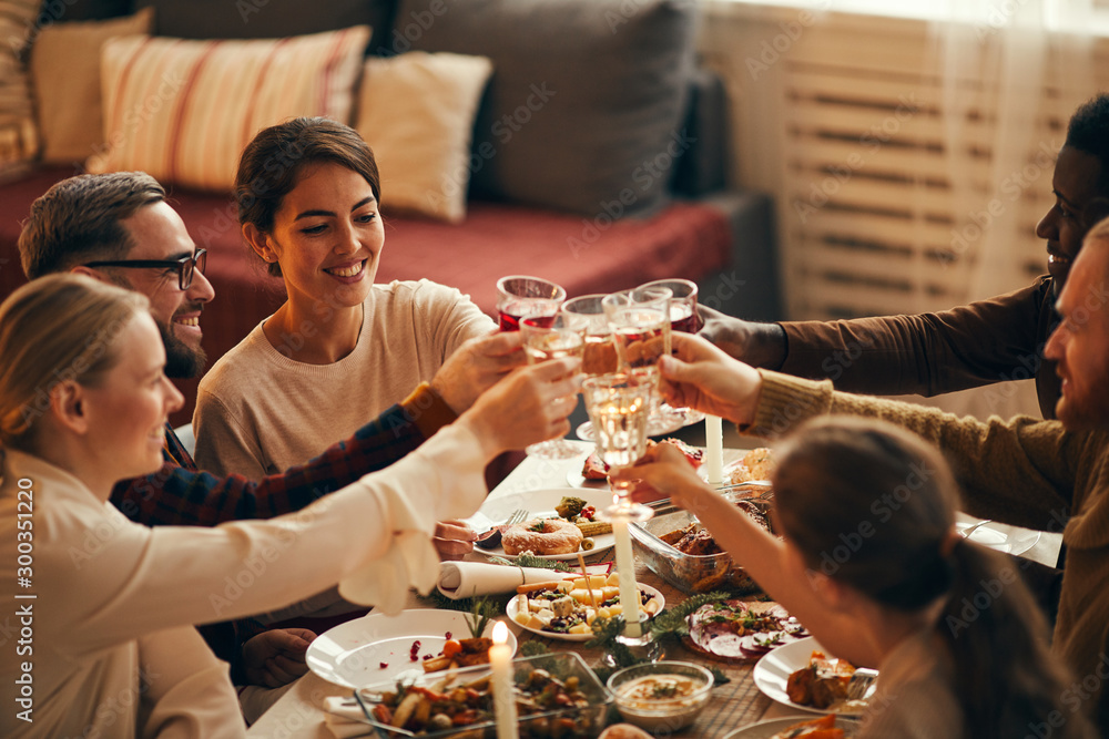 Fototapeta High angle view at elegant young people clinking champagne glasses while enjoying Christmas dinner at home, copy space
