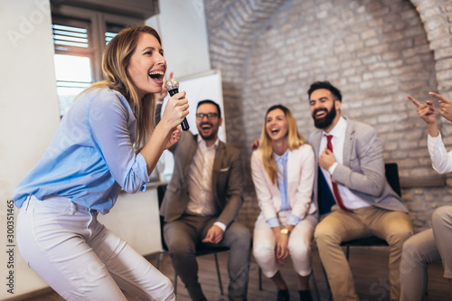 Valokuva  Business people making team training exercise during team building seminar singing karaoke
