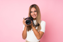 Young Blonde Woman Over Isolated Pink Background With A Professional Camera