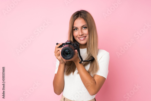 Obraz Young blonde woman over isolated pink background with a professional camera - fototapety do salonu
