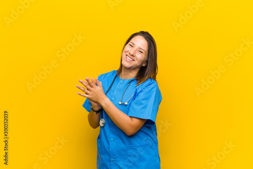 Photo feeling happy and successful, smiling and clapping hands, saying congratulations