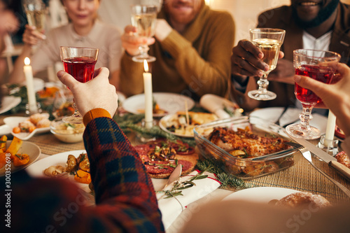 Close up of modern adult people raising glasses while enjoying Christmas dinner at home, copy space - 300352698