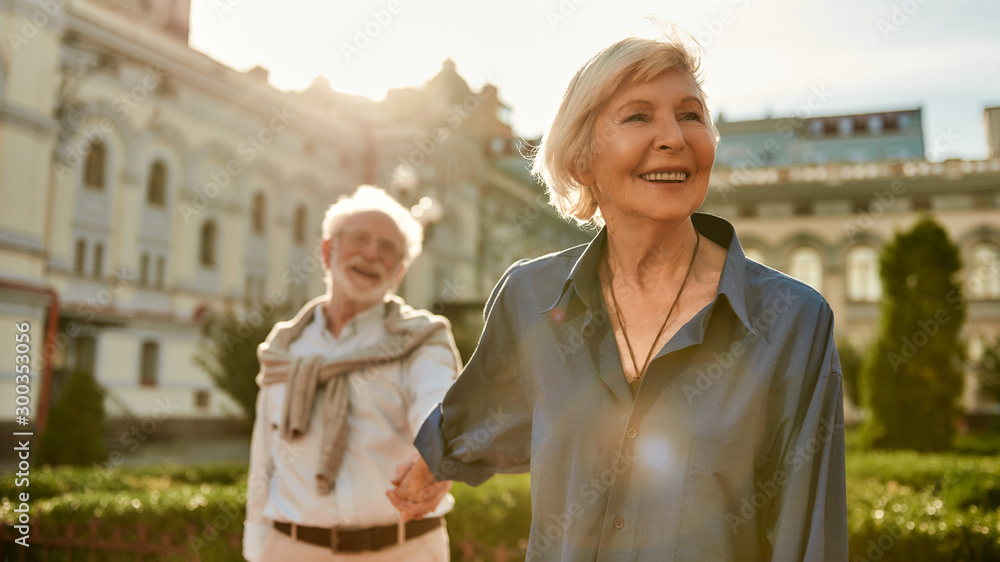 Fototapeta Your love is all I need. Beautiful and happy senior couple holding hands and smiling while spending time together outdoors