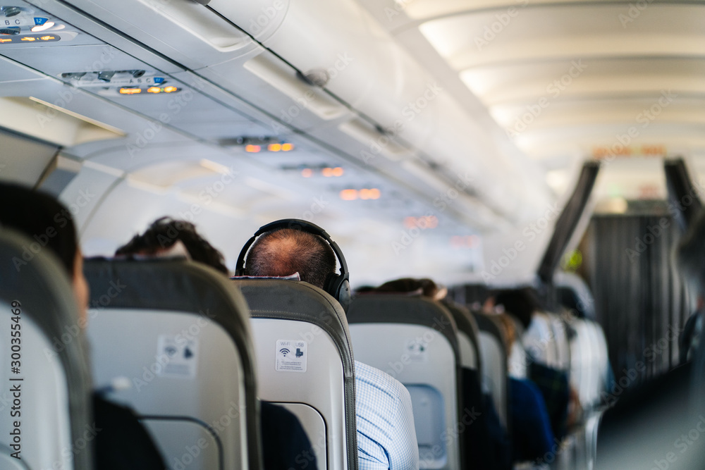 Fototapety, obrazy: man listens to music in headphones on a plane