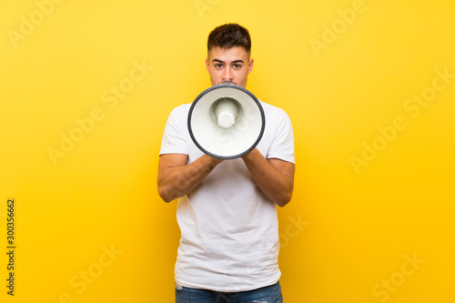 Young handsome man over isolated yellow background shouting through a megaphone Canvas Print
