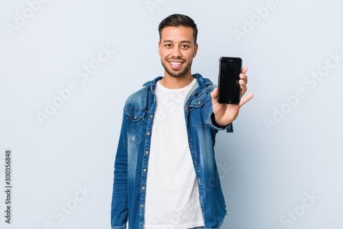 Obraz Young south-asian man holding a phone - fototapety do salonu