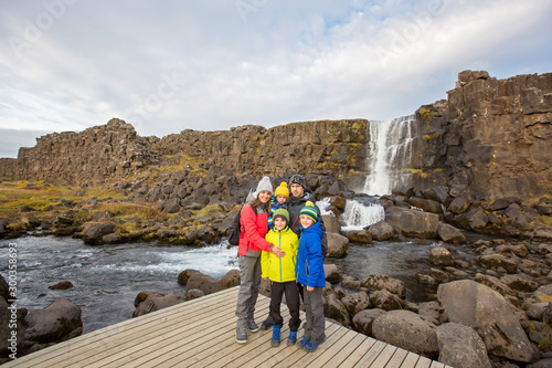 plakat Family, mother, father with three children, enjoying a sunny day in Thingvellir National Park rift valley, Iceland