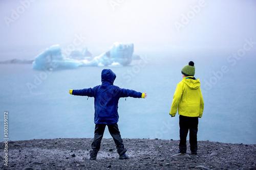 plakat Child, taking picture at early evening on a rainy day at picturesque iceberg lagoon Jokursarlon