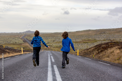 plakat Kids running on an empty road in beautiful nature in Snaefellsjokull National Park in Iceland, autumntime