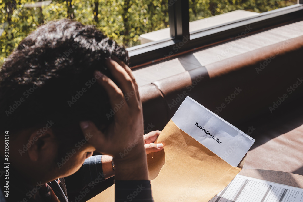 Fototapeta Stressed businessman feeling down after received Termination of Employment Form in paper brown envelope.