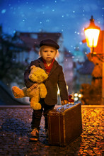 Beautiful Toddler Child With Lantern And Teddy Bear, Casually Dressed, Looking At Night View Of Prague City