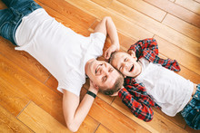 Father And Son, 8 Years Old Boy In Checkered Shirts Lie Head To Head On A Wooden Floor, Top View