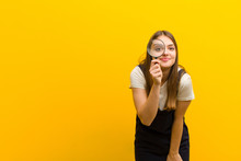 Young Pretty Woman  With A Magnifying Glass Against Orange Background