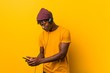 Young african man standing against a yellow background wearing a hat listening to music with a phone