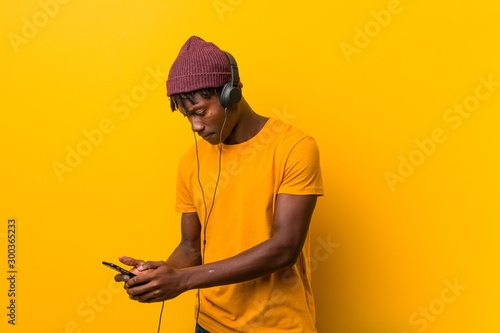 Fotografie, Obraz  Young african man standing against a yellow background wearing a hat listening t