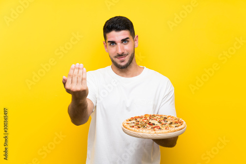 Photo Young handsome man holding a pizza over isolated yellow wall inviting to come with hand