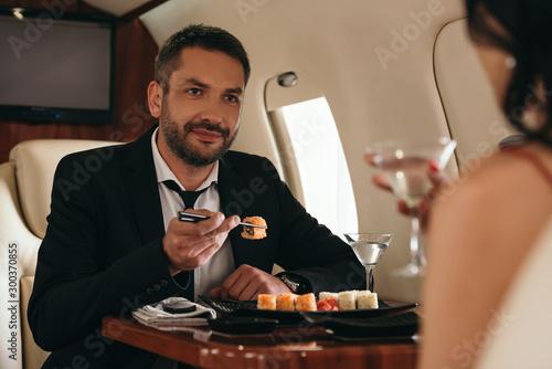 Fototapeta cropped view of woman holding martini glasses near handsome man in private jet obraz
