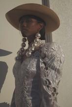 Model In White Formal Dress With Oversized Pearl Earrings