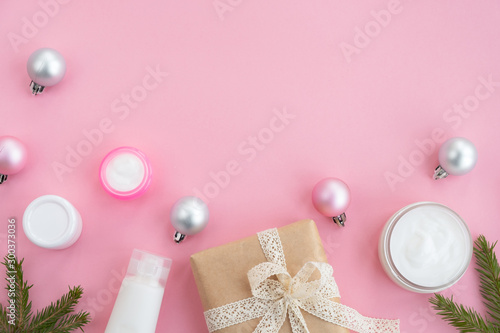 Fotografía  Cosmetic products, gift box and festive decor on a light pink background