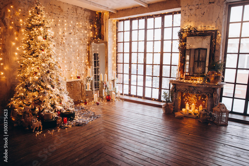 Tuinposter Oude gebouw warm cozy evening luxury Christmas room interior design, Xmas tree decorated by gold lights presents gifts, candles,mirror garland lighting fireplace.holiday living room. New year holidays concept