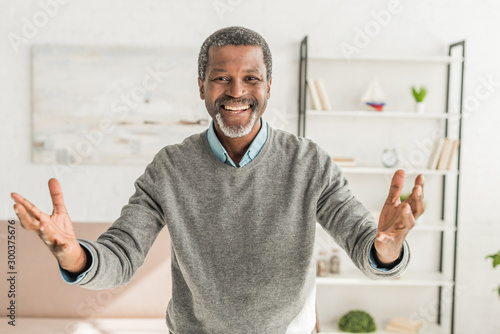 happy african american man looking at camera and showing welcome gesture Canvas Print