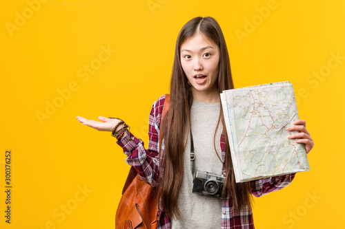 Fotografie, Obraz  Young asian woman holding a map impressed holding copy space on palm