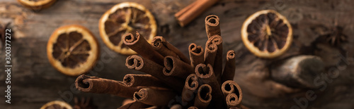 Fototapeta top view of dried citrus slices with cinnamon sticks on wooden background, panoramic shot obraz