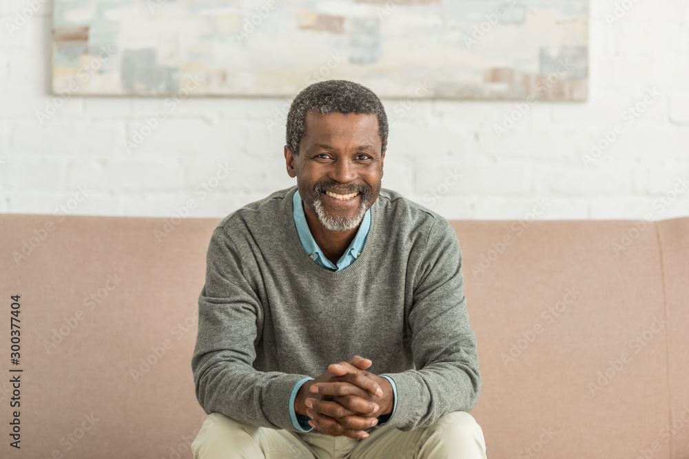 Fototapeta senior african american man sitting on sofa with clenched hands and smiling at camera