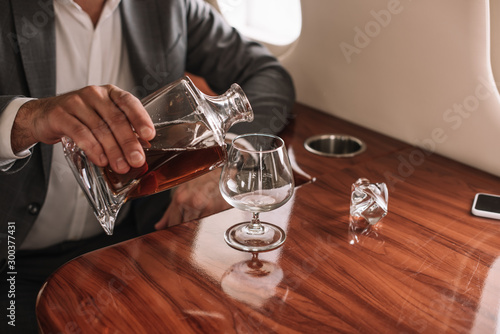 Canvas Prints Alcohol cropped view of businessman pouring cognac into glass in private jet