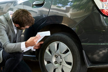Car Salesman Examining Car Tyre While Holding Documents