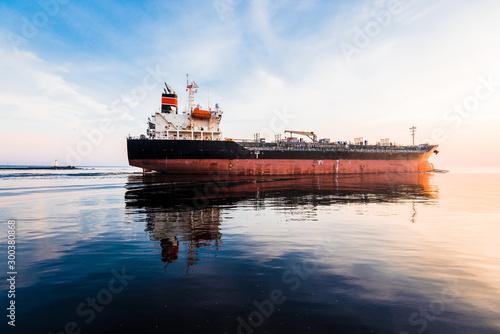 Fototapeta Крупный грузовой кран корабль на закате. Вечерние облака и яркий солнечный свет. Балтийское море, Латвия. Маяк на заднем плане obraz