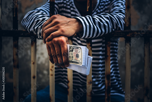 Vászonkép Male criminals Captured in a dirty cage On charges of counterfeiting a bank dollar, in which he held the fake banknote in his hand, to financial crime concept