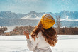Beautiful girl tossing snow against mountains