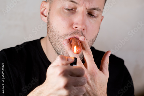 Fotografie, Tablou unshaven men holds a sausage in his mouth in the manner of a cigar