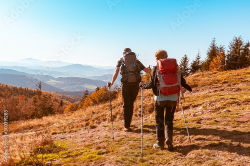 Fototapeta  Two old people with large backpacks hike through the autumn mountains, the conce