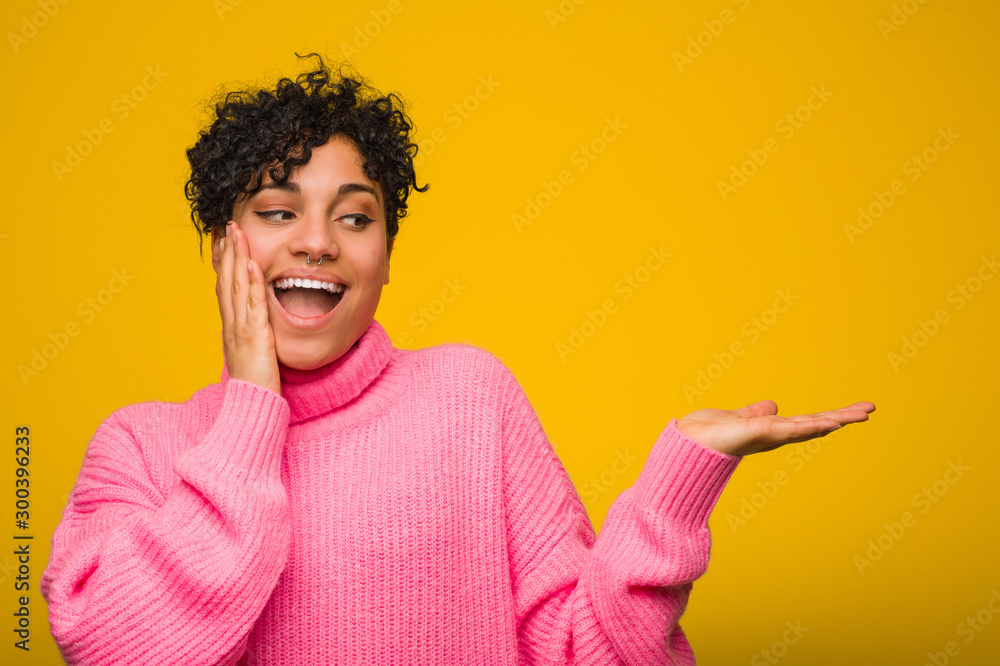 Fototapeta Young african american woman wearing a pink sweater holds copy space on a palm, keep hand over cheek. Amazed and delighted.
